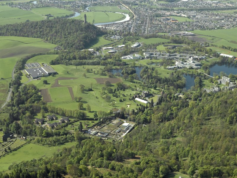 General oblique aerial view centred on the university, library, auditorium, halls of residence, bridge and factory with the country house and walled garden in the foreground, taken from the N.