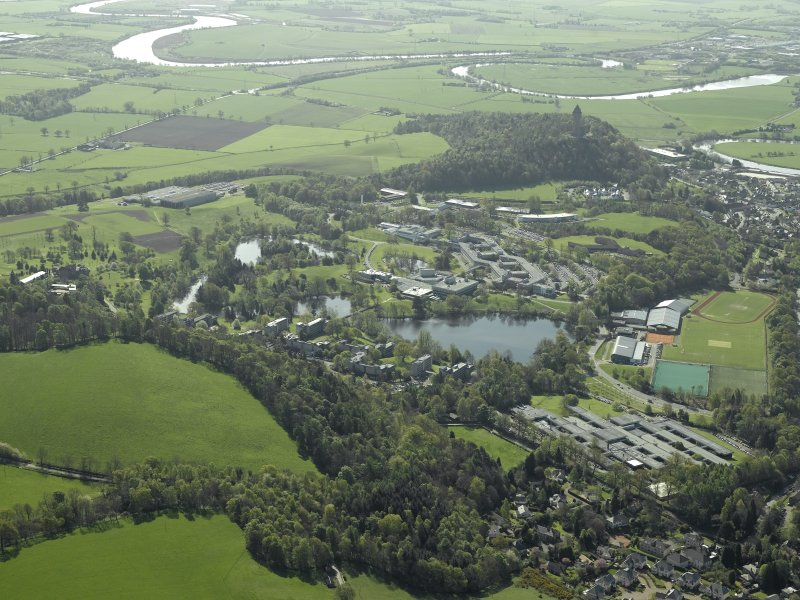 General oblique aerial view centred on Stirling University, library, auditorium, halls of residence, bridge and factory with Airthrey Castle adjacent, taken from the N.