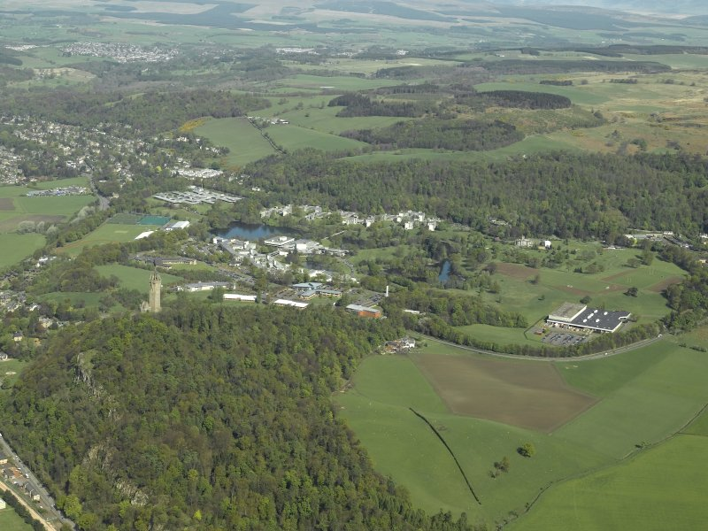 General oblique aerial view centred on the university, country house and factory with the monument in the foreground, taken from the SE.