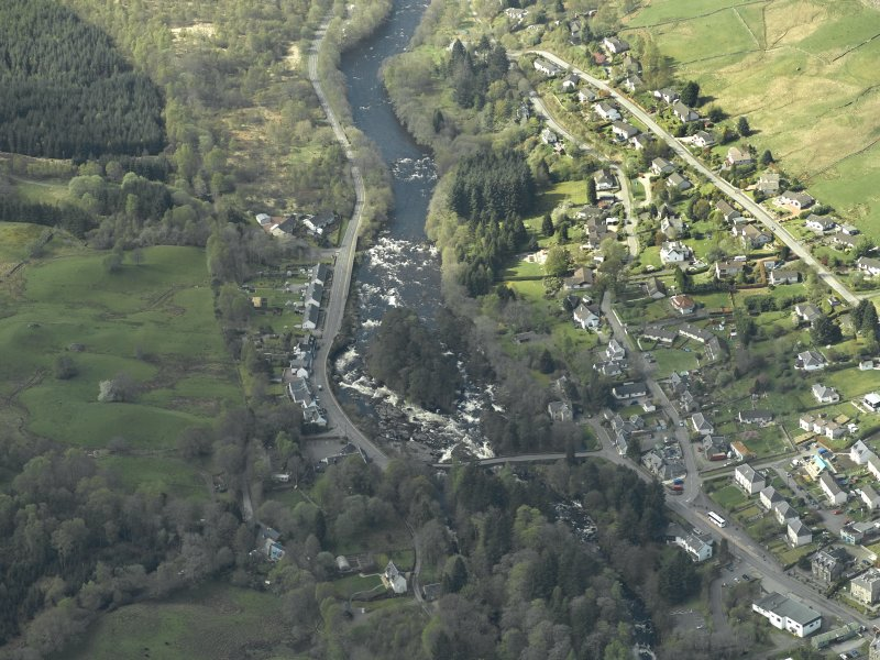 Oblique aerial view of the village centred on the road bridge, taken from the NE.