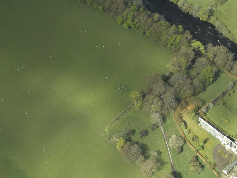 Oblique aerial view centred on the remains of the stone circle, taken from the E.