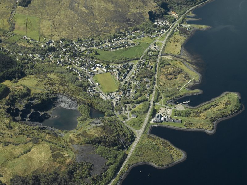 Oblique aerial view of the village centred on the harbour, slate quarries and remains of the fort, taken from the NE.