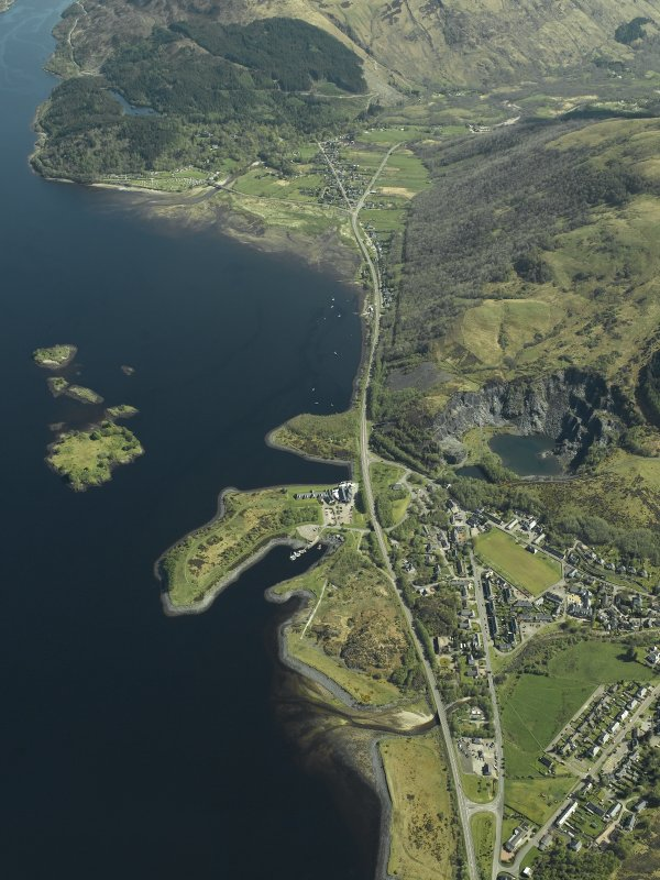 Oblique aerial view of the village centred on the harbour, slate quarries and remains of the fort, taken from the NNW.