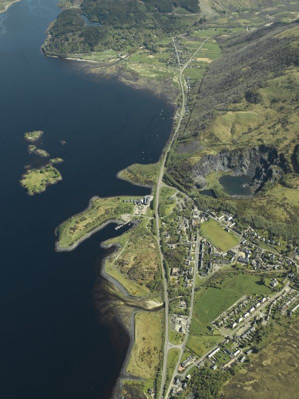 Oblique aerial view of the village centred on the harbour, slate quarries and remains of the fort, taken from the W.