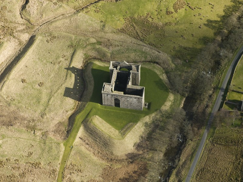 Oblique aerial view centred on Hermitage castle and moat, taken from the W.