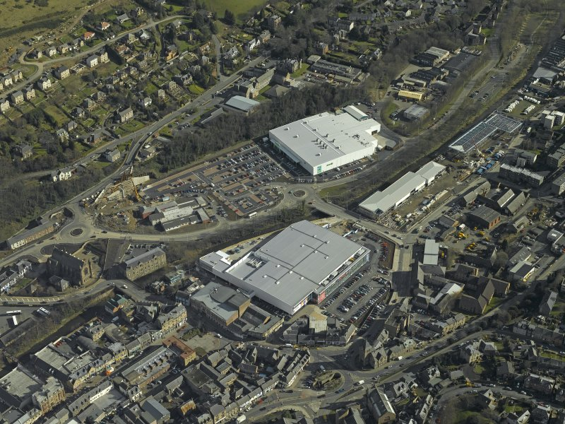 Oblique aerial view centred on the central and former station areas of Galashiels with the almost complete superstores, Tesco and Asda, taken from the NW.