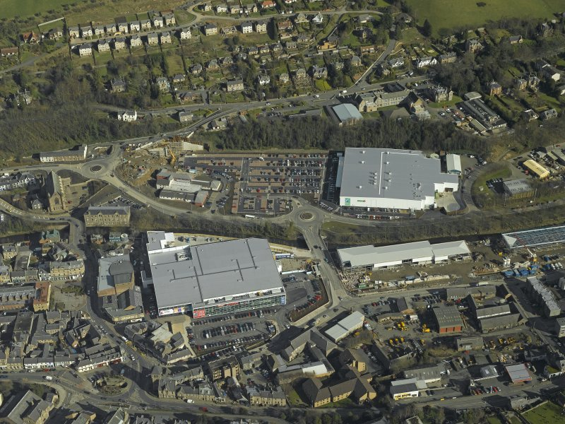 Oblique aerial view centred on the central and former station areas of Galashiels with the almost complete Suoerstores, Asda and Tesco, taken from the W.