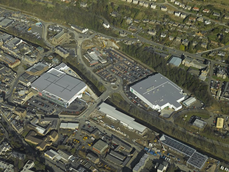 Oblique aerial view centred on the central and former station areas of Galashiels with the almost complete superstores, Asda and Tesco, taken from the SE.