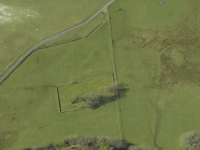 Oblique aerial view centred on the remains of the burial-ground, taken from the SE.