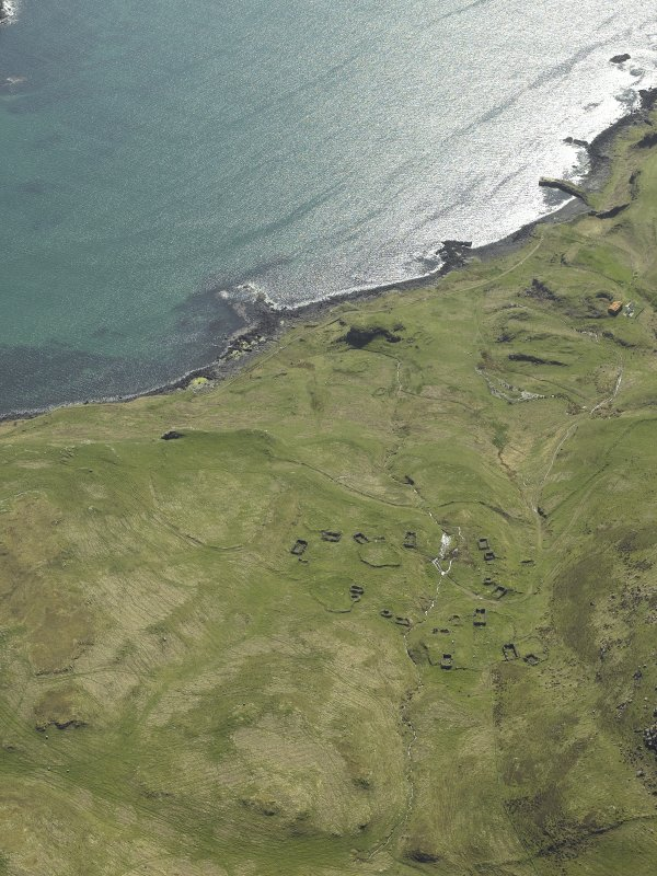 Oblique aerial view centred on the remains of the township with the remains of the dun adjacent, taken from the SE.