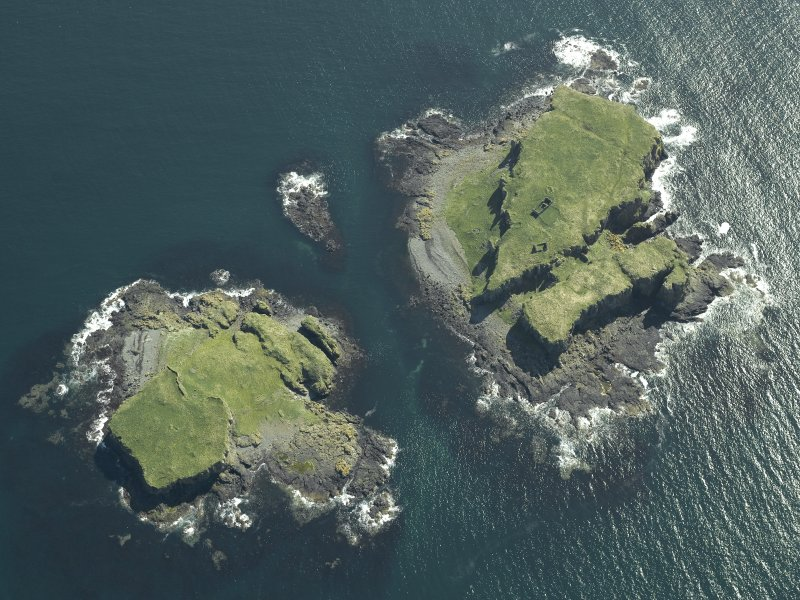 Oblique aerial view of the islands centred on the remains of the castles, taken from the N.