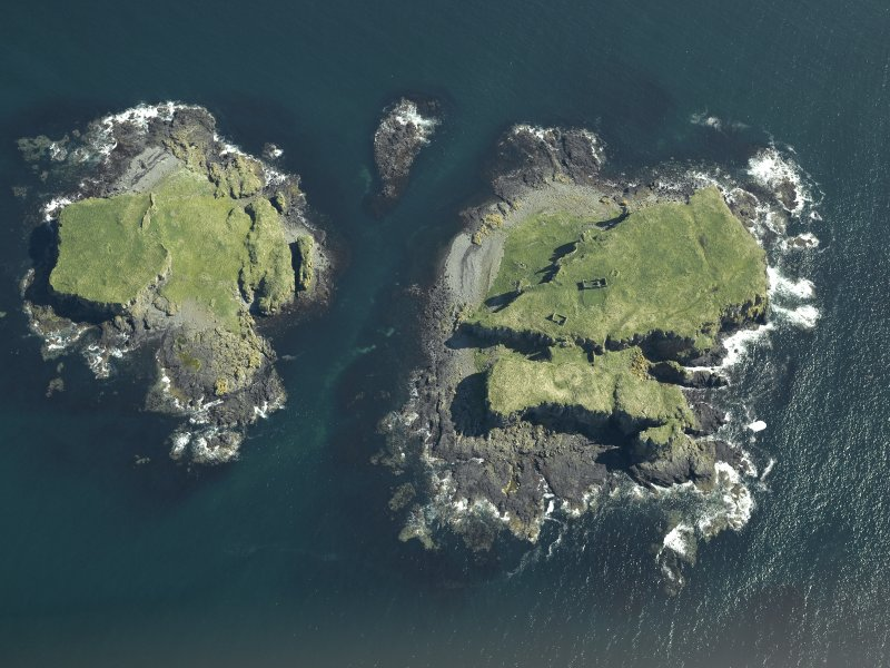 Oblique aerial view of the islands centred on the remains of the castles, taken from the NW.