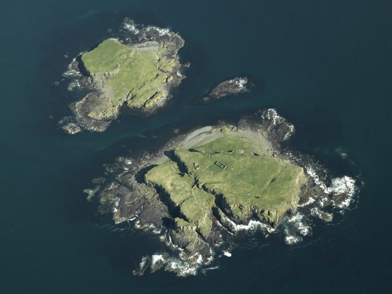 Oblique aerial view of the islands centred on the remains of the castles, taken from the W.