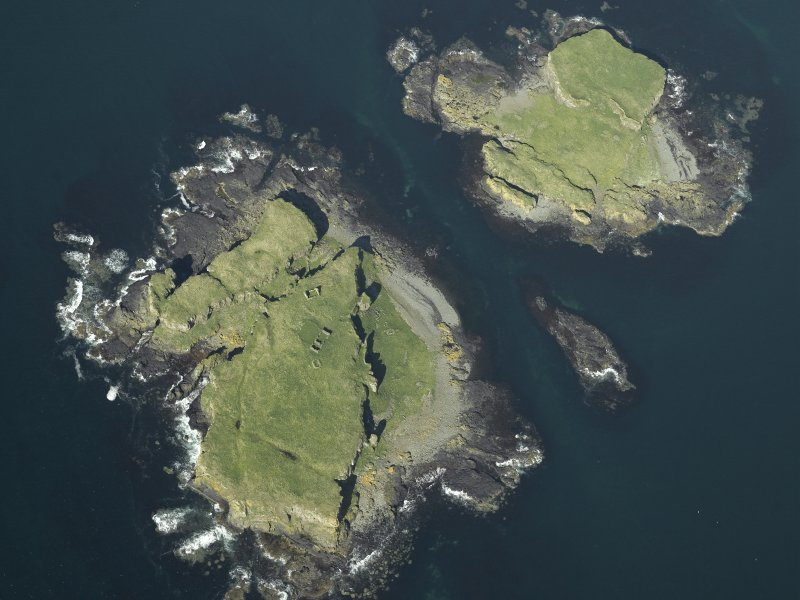 Oblique aerial view of the islands centred on the remains of the castles, taken from the SSW.