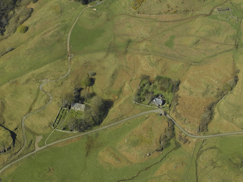 Oblique aerial view centred on the church and burial ground with the remains of the crofting township and field-system adjacent, taken from the S.