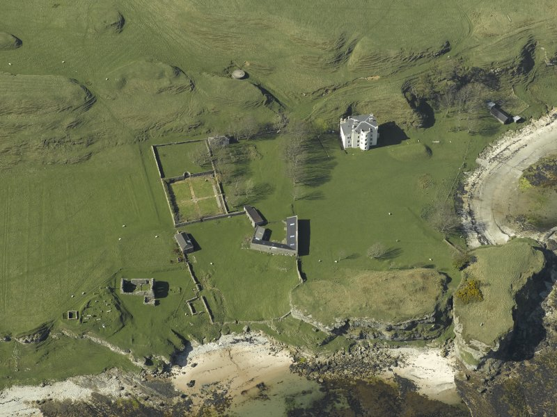 Oblique aerial view centred on the house and farmsteading and the remains of the church, burial-ground and cottage, taken from the SSE.