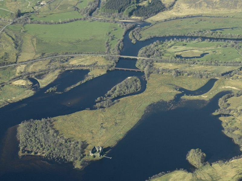 Oblique aerial view centred on the Awe rail bridge, Dalmally and the road bridge over River Orchy with the remains of Kilchurch Castle in the foreground, taken from the WSW.