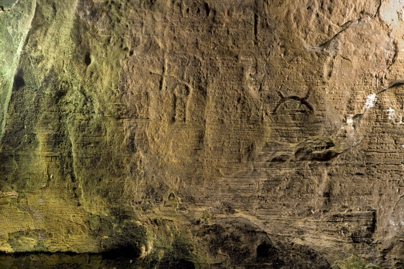 Detail of carving, including cross and crescent and V-rod Pictish symbol on wall of Sculptor's Cave, Covesea