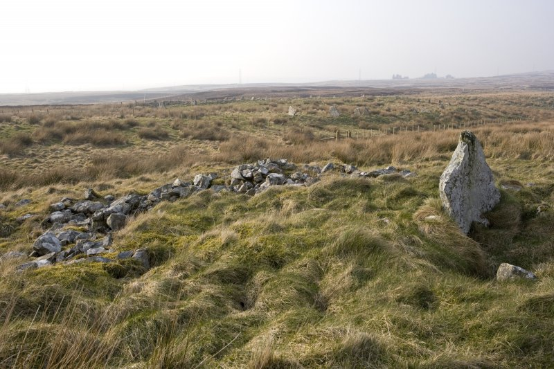 The cairn and chamber from the SE, with Achkinloch stone setting (ND14SE 2) in the background.