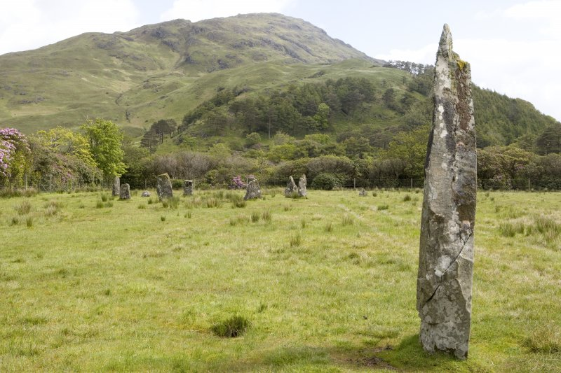 Standing stone with stone circle in background, view from W
