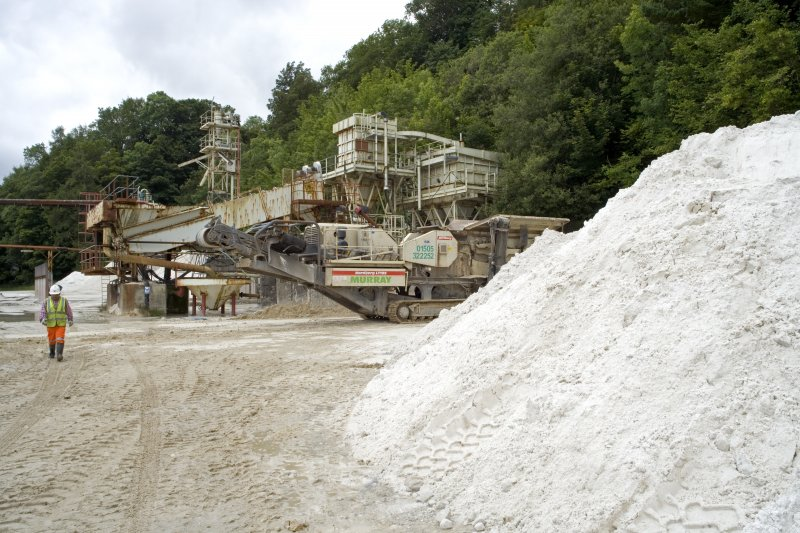 View of Eagle screw and flotation plant and raw sand stock awaiting crushing. The raw stock to the left of the picture has just been extracted from the mine.