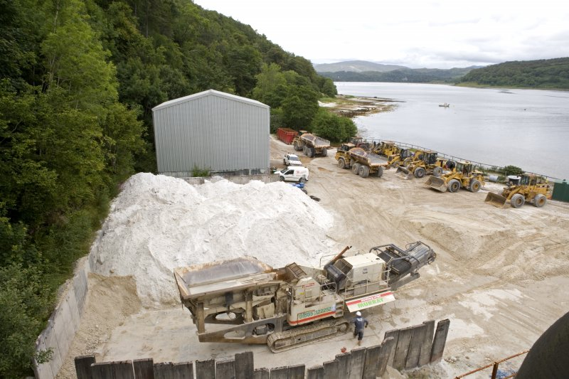 Elevated view from S of portable primary crusher, Raw Sand Stockpile and workshops beyond.