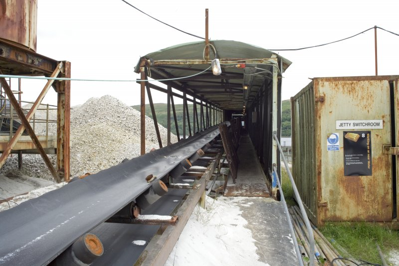 View from W looking along Conveyor No. 4 which carries stockpiled processed sand to the boat over a weighbridge. The switroom is housed in a container adjacent.