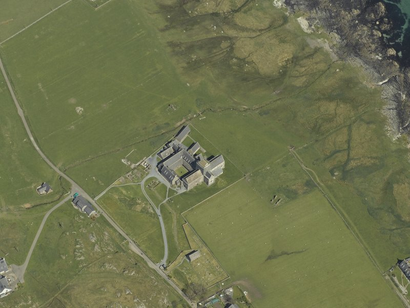 Oblique aerial view centred on the abbey and the remains of the vallum, taken from the SW.