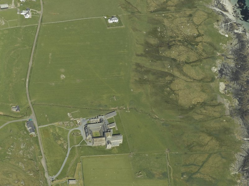 Oblique aerial view centred on the abbey and the remains of the vallum with the house adjacent, taken from the SSW.