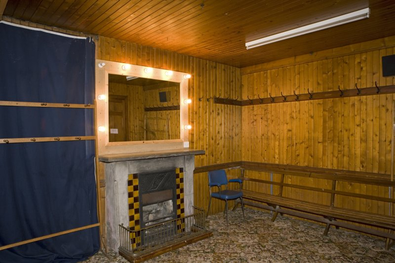 Interior. Under stage area, view of  timber lined dressing room with chimneypiece