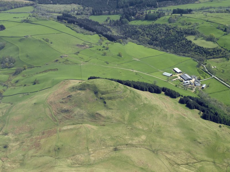 Oblique aerial view centred on the remains of the hillfort, taken from the NW.