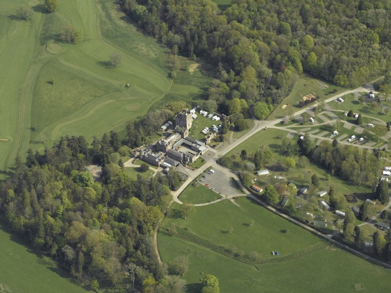 Oblique aerial view centred on the country house with the caravan park adjacent, taken from the NW.
