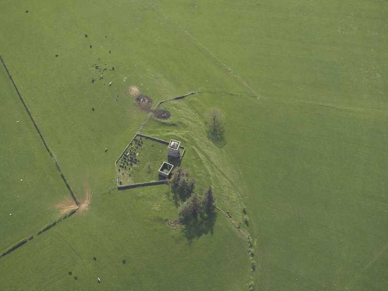 Oblique aerial view centred on the ruins of the tower house and chapel and the graveyard, taken from the E.