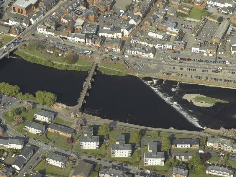 Oblique aerial view centred on the road bridge and weir, taken from the SW.