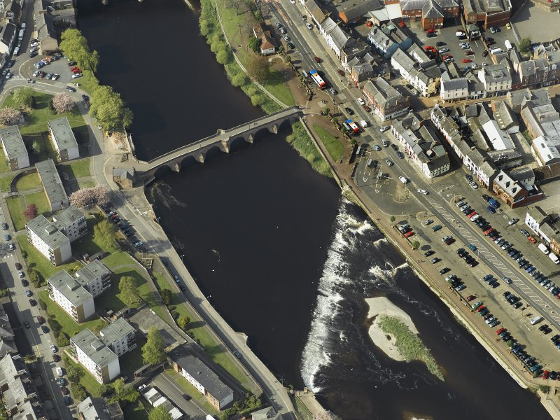 Oblique aerial view centred on the road bridge and weir, taken from the SSE.