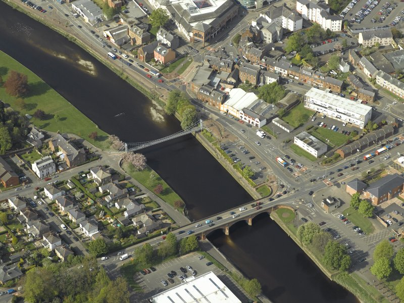 Oblique aerial view centred on the road bridge and suspension bridge, taken from the S.