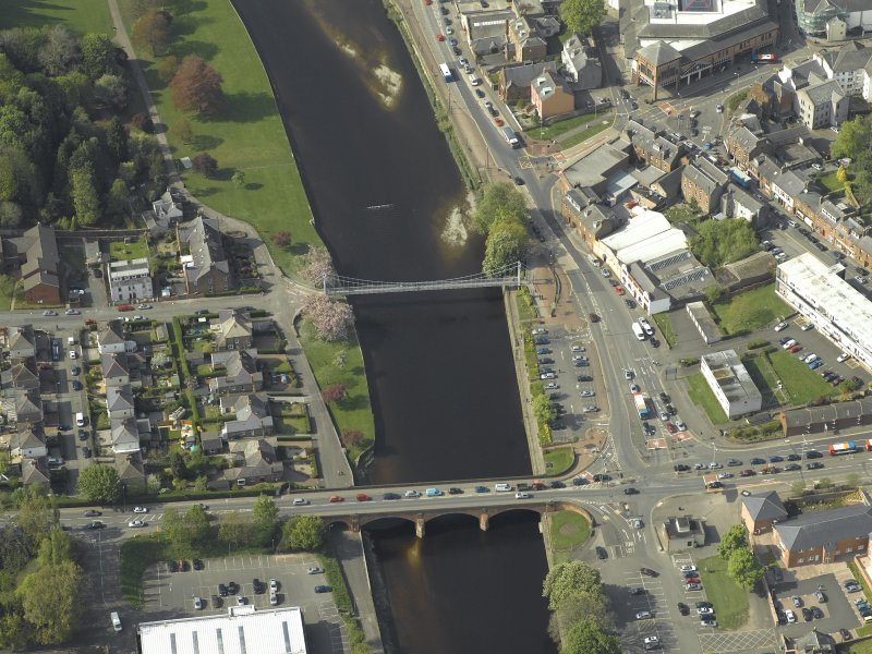 Oblique aerial view centred on the road bridge and suspension bridge, taken from the SE.