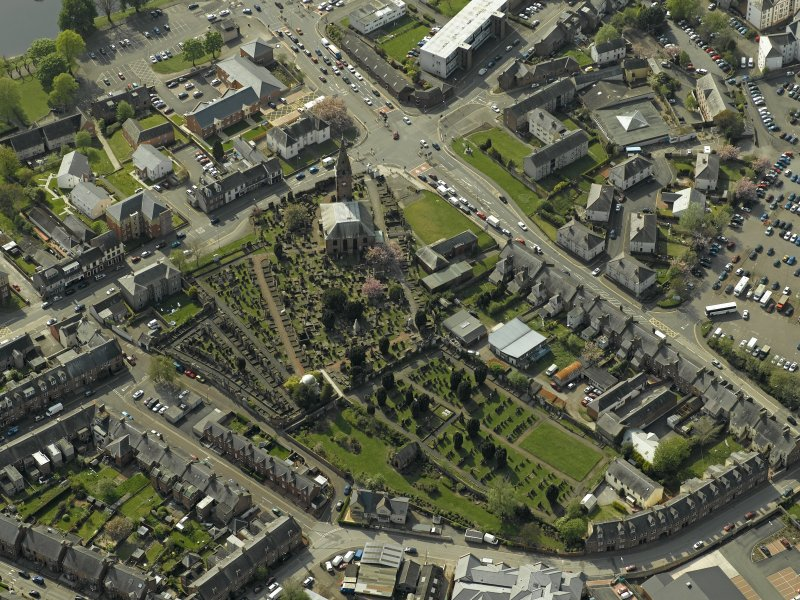 Oblique aerial view centred on the church and graveyard, taken from the E.