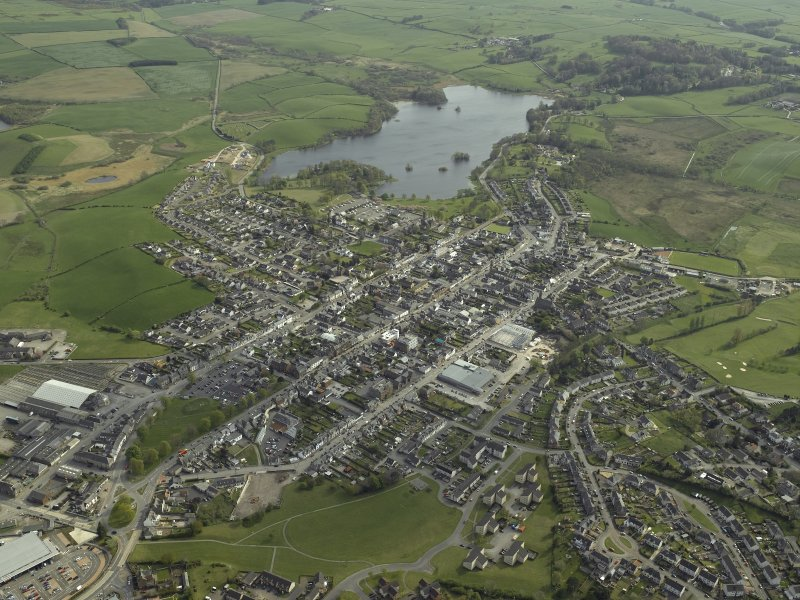 General oblique aerial view of the town with Carlingwark Loch beyond, taken from the NNW.