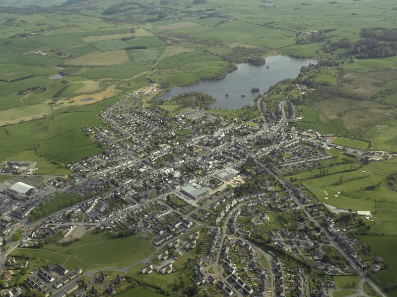 General oblique aerial view of the town with Carlingwark Loch beyond, taken from the NW.