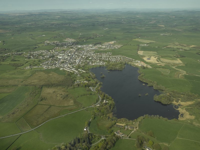 General oblique aerial view of the town with Carlingwark Loch in the foreground, taken from the SW.
