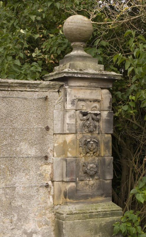 Detail of gate pier to NE of main house showing carved stonework and ball finial from S.