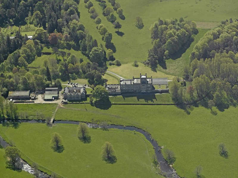 Oblique aerial view centred on the house with stable block and farm adjacent, taken from the N.
