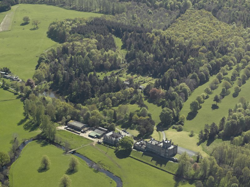 Oblique aerial view centred on the house with stable block and farm adjacent, taken from the NW.