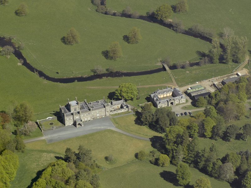 Oblique aerial view centred on the house with stable block and farm adjacent, taken from the S.