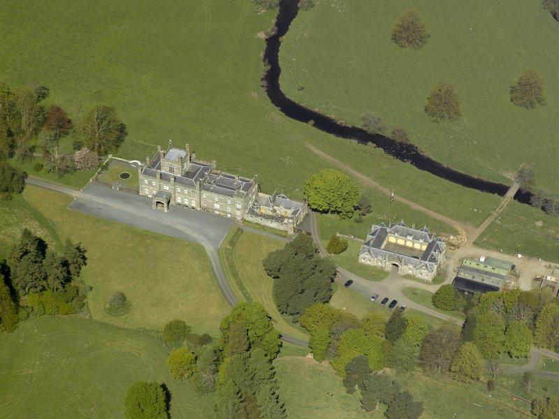Oblique aerial view centred on the house with stable block and farm adjacent, taken from the SSE.