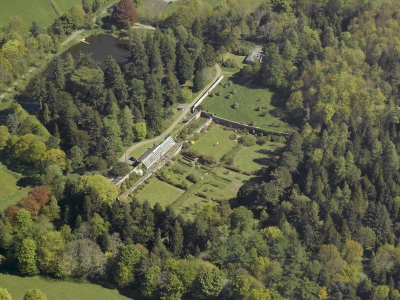 Oblique aerial view centred on the house with stable block and farm adjacent, taken from the SW.
