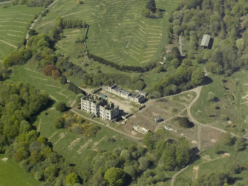 Oblique aerial view centred on the ruins of the country house, taken from the E.