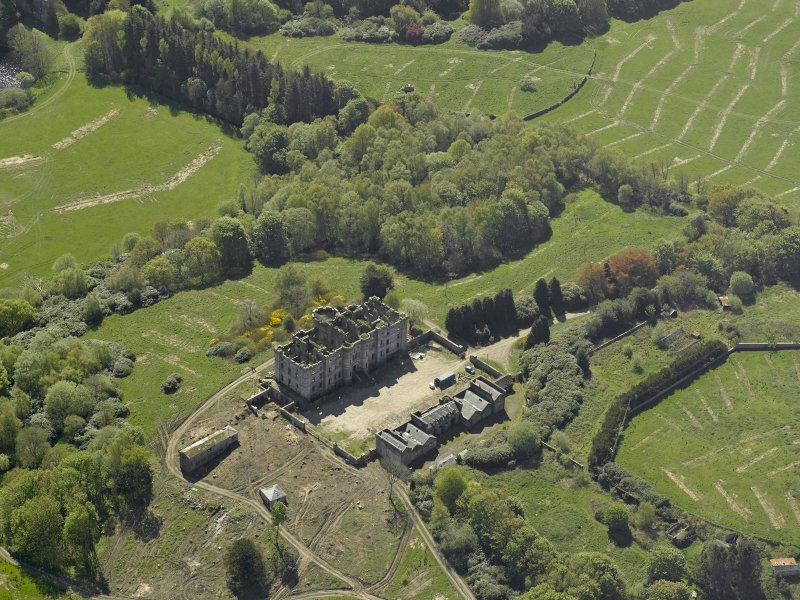 Oblique aerial view centred on the ruins of the country house, taken from the NNW.