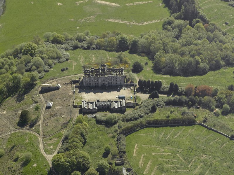 Oblique aerial view centred on the ruins of the country house, taken from the NW.